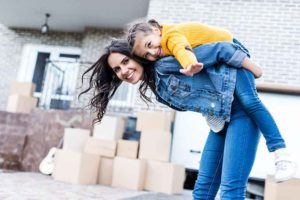 mother young daughter in front of new home
