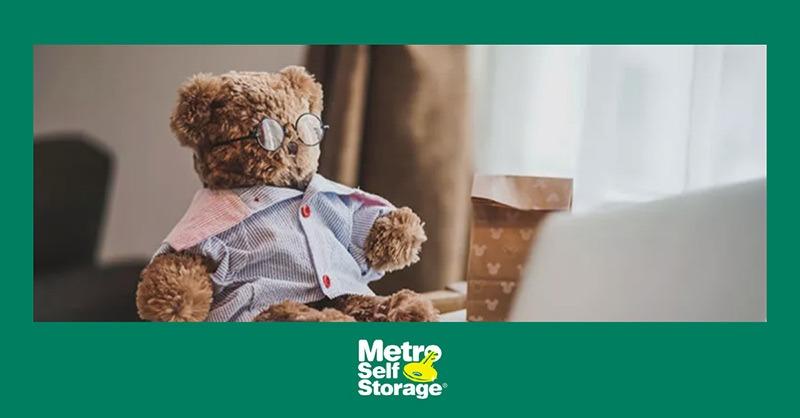 Photo of teddy bear sitting on desk near laptop
