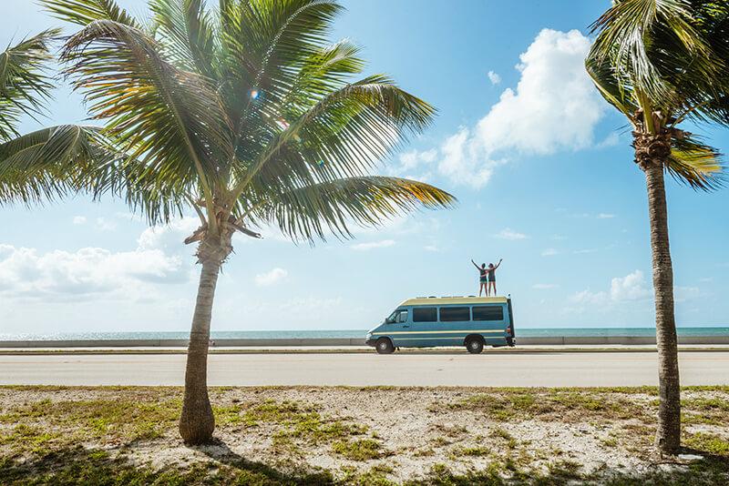 couple standing on camper van overlooking ocean