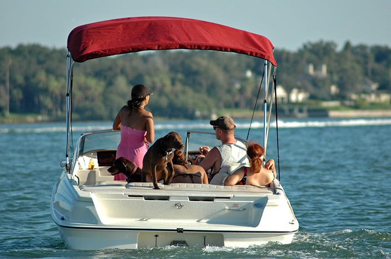 family enjoying time on a lake in a covered boat