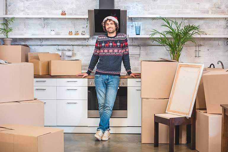 young man leaning on counter surrounded by moving boxes cheap brooklyn storage lockers blog