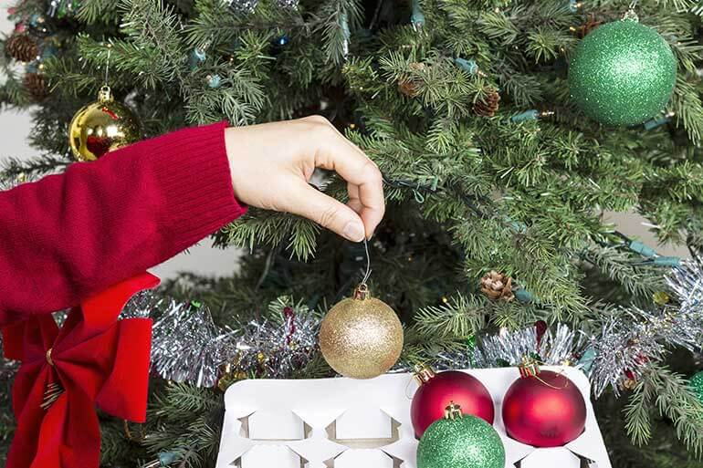 woman putting away christmas ornaments in a box