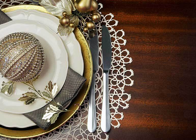 silver and gold ornate holiday place setting on wooden table