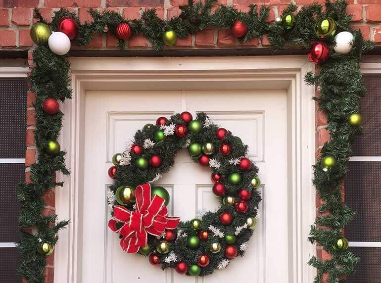 Christmas garland draping front door with wreath