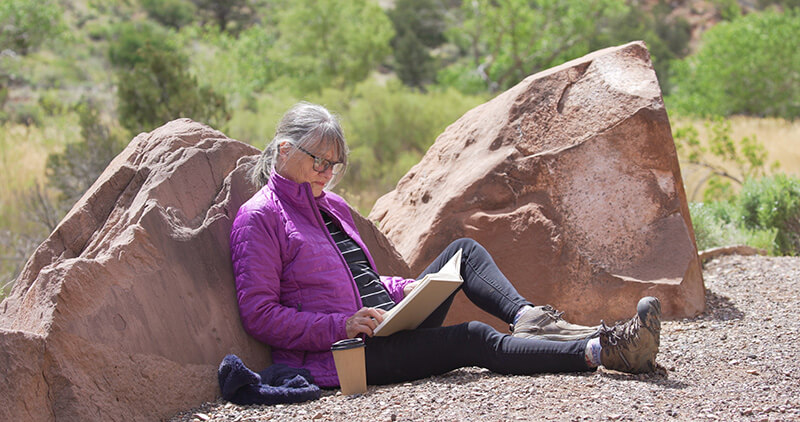 woman leaning on rock reading a book
