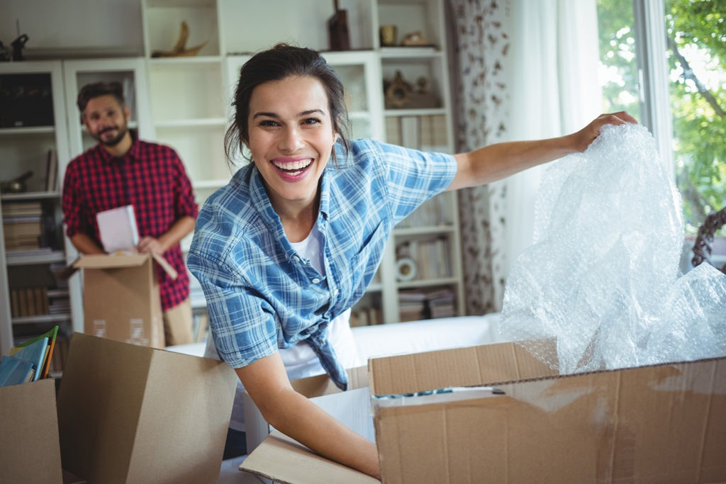 smiling woman packing moving boxes in living room