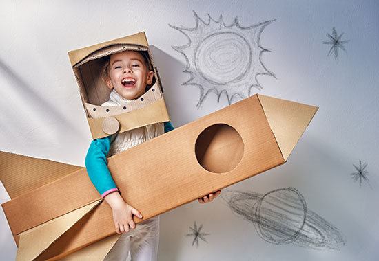 little boy posing with homemade cardboard rocket made out of moving boxes