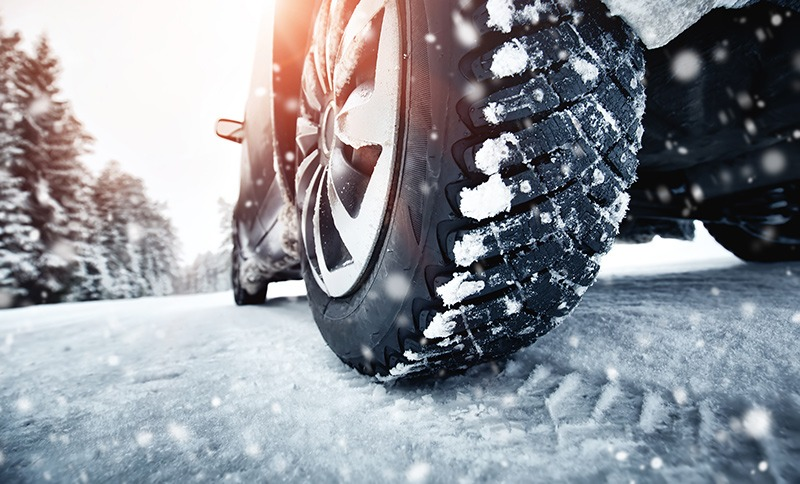 close up of snow tires on a car driving during a winter move to a new home