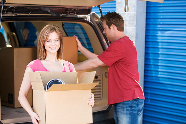 man and smiling woman loading storage unit