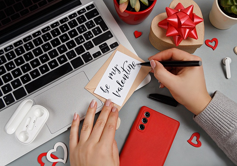 woman writing valentines day card near laptop and smart phone