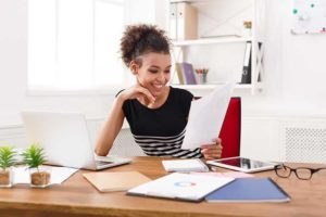 happy black woman working in home office on laptop
