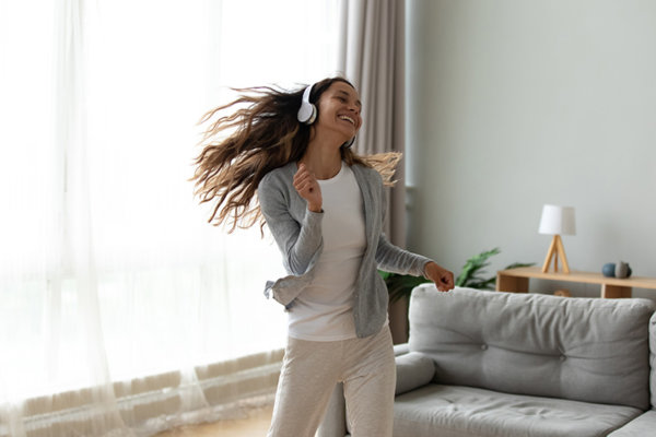 young woman wearing headphones dancing in apartment