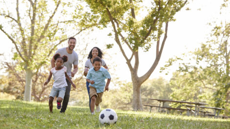 Black family playing soccer in the park together