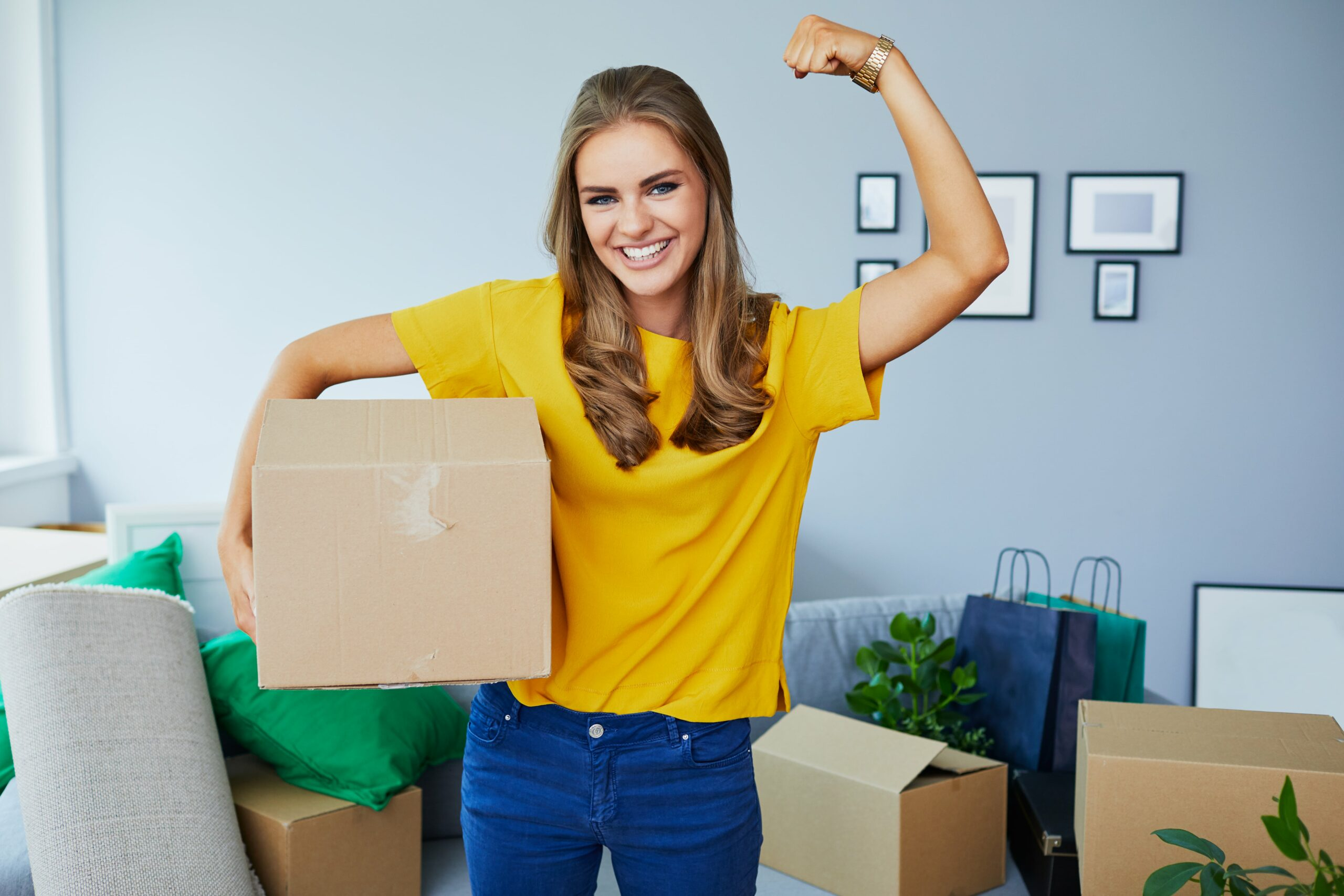girl in yellow shirt flexing arm in victory while holding a box.
