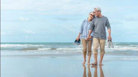 Elderly couple holding hands while walking on the beach.