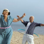 Mature couple hula-hooping on the beach.