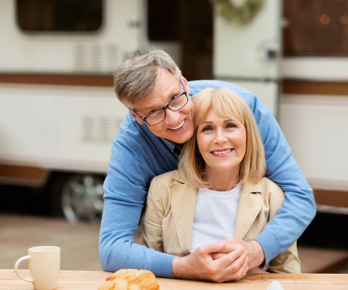 Snowbird couple embracing each other in front of RV.